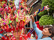 "23 JUNE 2015 - MAHACHAI, SAMUT SAKHON, THAILAND:  A toy vendor at the City Pillar Shrine procession in Mahachai. The Chaopho Lak Mueang Procession (City Pillar Shrine Procession) is a religious festival that takes place in June in front of city hall in Mahachai. The ""Chaopho Lak Mueang"" is  placed on a fishing boat and taken across the Tha Chin River from Talat Maha Chai to Tha Chalom in the area of Wat Suwannaram and then paraded through the community before returning to the temple in Mahachai.  PHOTO BY JACK KURTZ"