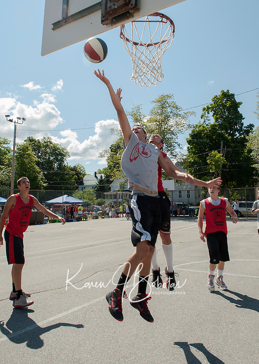Team Something's Jake Sullivan guarded by Summer Ball's David Mahoney go up for a shot during the Bob Dearborn 3 on 3 Memorial Basketball Tournament held at Wyatt Park Saturday.  (Karen Bobotas/for the Laconia Daily Sun)