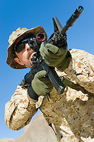 Soldier aiming rifle outdoors (low angle view)