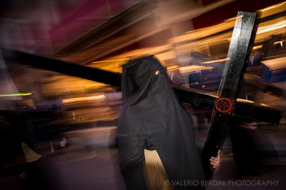 "San Isidoro Brotherhood in the evening of Good Friday in Cuna, a central street in Sevilla. Here ""Nazarenos"", dressed with the ""capirote"" and a full black tunic  make penance carrying along the procession either long (and heavy) Paschal candles or wooden crosses."