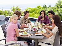 Friends sitting around patio table socialising eating and drinking