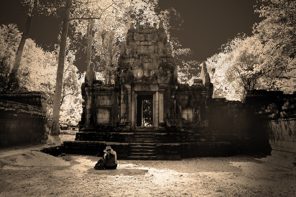 The image portrays the mystical charm of Angkor Thom. It shows a woman sat reading in total silence and solitude.