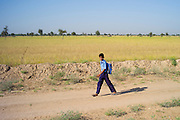 Young Indian boy in school uniform walking barefoot to school near Rohet in Rajasthan, Northern India