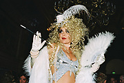 Woman with blonde curly wig, feathered fan, silver top and long cigarette holding, Posh at Addington Palace, UK, August, 2004