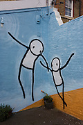 Mural by the artist known as Stik, painted on a wall at Push Studios, Blackwater Street, East Dulwich. Stik people, although androgenous and constructed from simple shapes, are nevertheless capable of conveying complex body language and emotion. These themes of human emotion and expression are infused in Stiks brightly coloured street art. Stik, the street artist, himself was homeless for a period and ideas surrounding human vulnerability are also detectable in his art. Stik has been creating Stik people around London for over ten years