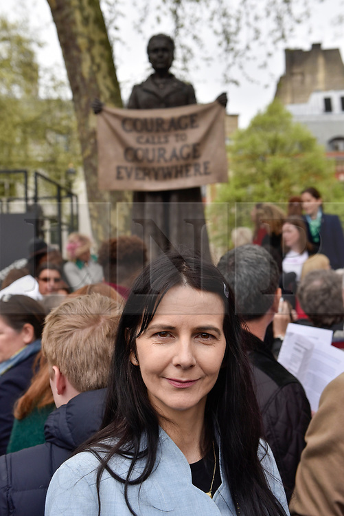 """© Licensed to London News Pictures. 24/04/2018. LONDON, UK. Artist Gillian Wearing poses at the unveiling of a statue of suffragist Millicent Fawcett in Parliament Square.  The bronze casting, created by artist Gillian Wearing, shows a banner reading the text """"courage call to courage everywhere"""", is the first statue of a woman to be erected in Parliament Square and was commissioned as part of this year's centenary of the 1918 Representation of the People Act, giving some women aged over 30 the right to vote.  Photo credit: Stephen Chung/LNP"""