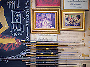 "25 MAY 2015 - BANGKOK, THAILAND: Pictures of Ajarn Neng Onnut and some of Ajarn Neng's tattoo needles in his Sak Yant tattoo parlor. Sak Yant (Thai for ""tattoos of mystical drawings"" sak=tattoo, yantra=mystical drawing) tattoos are popular throughout Thailand, Cambodia, Laos and Myanmar. The tattoos are believed to impart magical powers to the people who have them. People get the tattoos to address specific needs. For example, a business person would get a tattoo to make his business successful, and a soldier would get a tattoo to help him in battle. The tattoos are blessed by monks or people who have magical powers. Ajarn Neng, a revered tattoo master in Bangkok, uses stainless steel needles to tattoo, other tattoo masters use bamboo needles. The tattoos are growing in popularity with tourists, but Thai religious leaders try to discourage tattoo masters from giving tourists tattoos for ornamental reasons.       PHOTO BY JACK KURTZ"