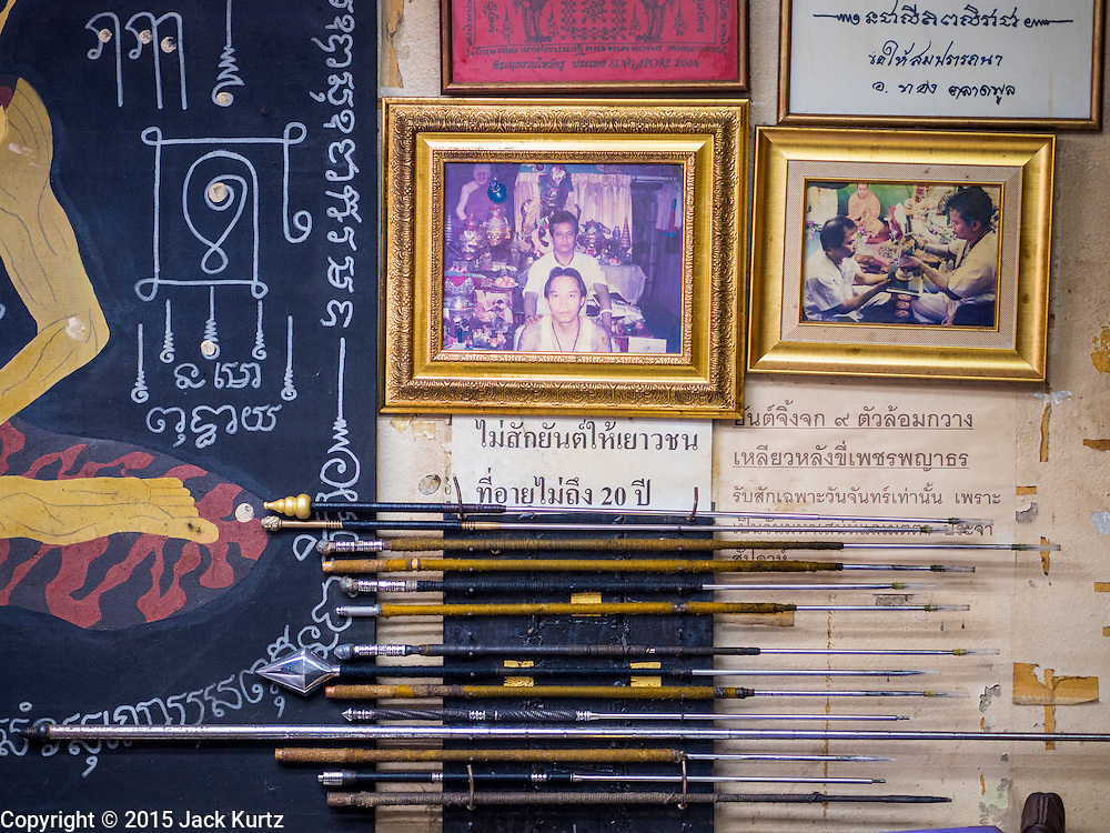 """25 MAY 2015 - BANGKOK, THAILAND: Pictures of Ajarn Neng Onnut and some of Ajarn Neng's tattoo needles in his Sak Yant tattoo parlor. Sak Yant (Thai for """"tattoos of mystical drawings"""" sak=tattoo, yantra=mystical drawing) tattoos are popular throughout Thailand, Cambodia, Laos and Myanmar. The tattoos are believed to impart magical powers to the people who have them. People get the tattoos to address specific needs. For example, a business person would get a tattoo to make his business successful, and a soldier would get a tattoo to help him in battle. The tattoos are blessed by monks or people who have magical powers. Ajarn Neng, a revered tattoo master in Bangkok, uses stainless steel needles to tattoo, other tattoo masters use bamboo needles. The tattoos are growing in popularity with tourists, but Thai religious leaders try to discourage tattoo masters from giving tourists tattoos for ornamental reasons.       PHOTO BY JACK KURTZ"""