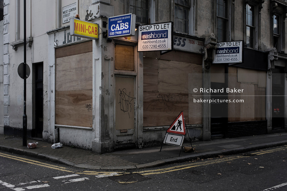 Desaturated image of boarded up central London mini cab business and an End of works sign on street corner.