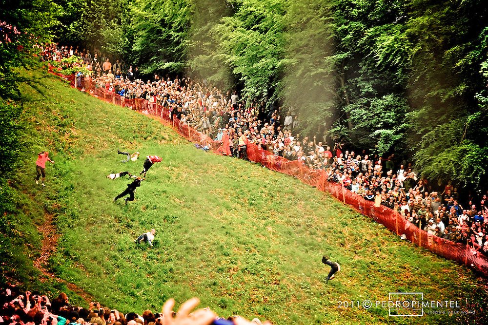 Cheese Rolling Festival. Competitors attempt to keep up with their legs in the impossible task of catching the rolling cheese during the traditional Gloucestershire Cheese Rolling festival. Cooper's Hill, UK.