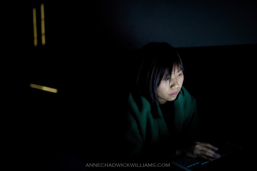 Thu Nguyen searches for jobs on her laptop while her daughters Amelie and Mia sleep at Trinity Episcopal Cathedral as part of the Family Promise program for the homeless in Sacramento, CA on March 6, 2008.