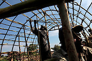 Men build a hut at Mungote camp for IDPs (Internally Displaced Persons) in Kichanga, 70km north of Goma, DRC on April 25, 2010. The long war had involved 9 African nations and claimed an estimated three million lives as a result of fighting or disease and malnutrition..Photo by Kuni Takahashi