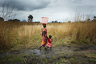 Argentina Adriano on her way home after collecting water with her son Dario Antonio and her daughter Arnela Antonio, Namissimbe, Mozambique