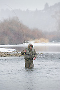 An angler casts a fly for trout during a snowstorm on the South Fork of the Snake River, Idaho.