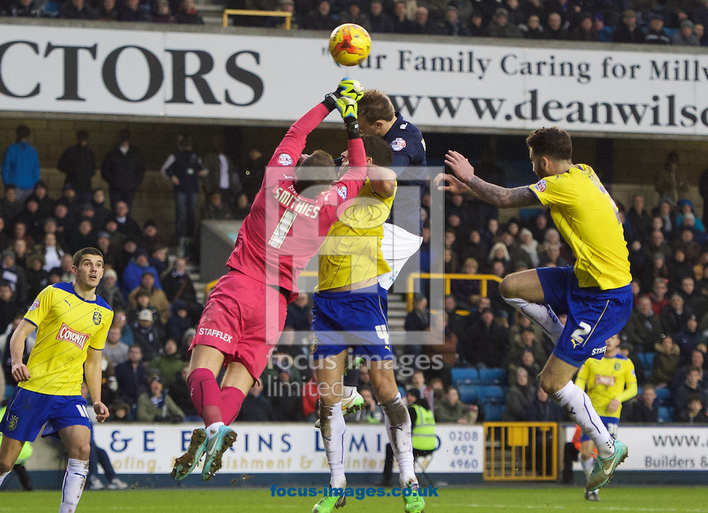 Goalkeeper Alex Smithies of Huddersfield Town punches the ball clear of Mark Beevers of Millwall during the Sky Bet Championship match at The Den, London<br /> Picture by Alan Stanford/Focus Images Ltd +44 7915 056117<br /> 07/02/2015