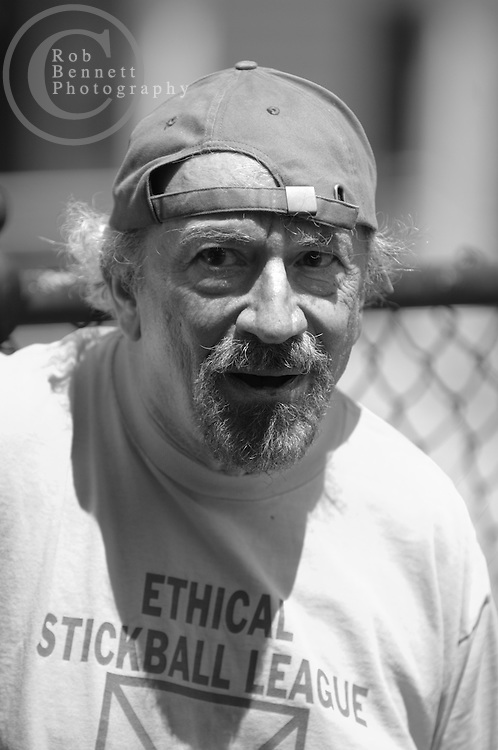 """Stefan """"The Wise One"""" Kanfer, an author from Hastings-on-Hudson, in the """"field"""" during a game of stickball..---.The Ethical Stickball League has been operating since 1970, meeting every Sunday in the parking lot behind Hastings High School from 10:30AM to 1PM.  The players are men now mostly in their 70s - carrying nicknames like """"The Wise One"""", """"Hit Man"""" and """"Plays Hurt"""" - who have an affiliation with the school, either as former teachers, students or neighbors. As their slogan suggests, all it takes for a few hours of """"Aestas Aeterna"""" (Eternal Summer) is an outside temperature above 45 degrees and 8 willing souls...CREDIT: Rob Bennett for The NY Times"""