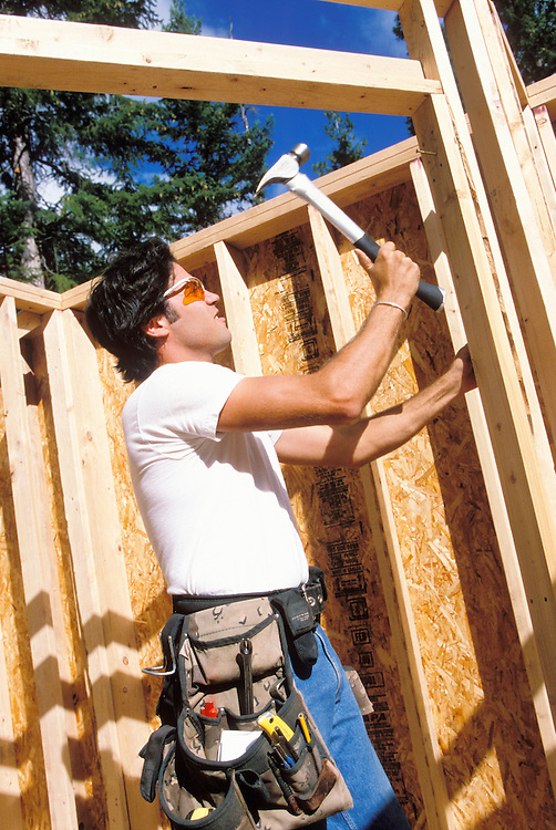 Young man hammering a nail in a construction  site.