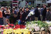 Crowds walk past fresh roses and lillies in Columbia Street flower market, in north London.