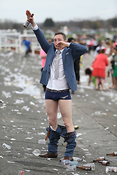 © Licensed to London News Pictures. 08/04/2016. Liverpool, UK. A racegoer salutes with his pants down on Ladies Day at the Grand National 2016 at Aintree Racecourse near Liverpool. The race, which was first run in 1839, is the most valuable jump race in Europe. Photo credit : LNP