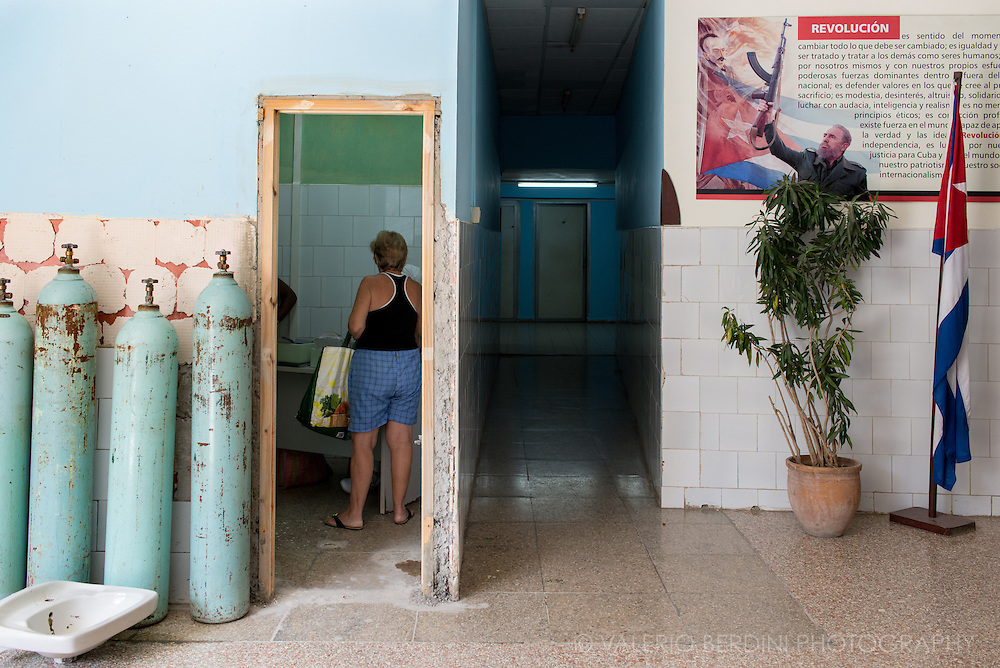 A woman inside a hospital in Havana, waiting for a doctor. Some oygen cilinders and a sink are left on the floor. A propaganda poster hangs on the wall. Healthcare in Cuba is completely free for the whole population. 2015