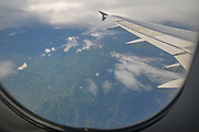 Elevated view of the Greece, the Mediterranean coast and clouds as seen through the window of an Airbus A320-200 plane