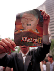 CHINA SHANGHAI 9MAY99 - A Chinese demonstrator holds up a poster with a carricature of US President Bill Clinton depicting him with features of Nazi leader Adolf Hitler in Shanghai May 9. Several thousand protesters gathered on Shanghai's streets today demonstrating against NATO's bombing of the Chinese embassy in Belgrade.       jre/Photo by Jiri Rezac