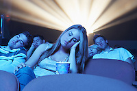 young People sleeping head on hand shoulder in Movie Theatre