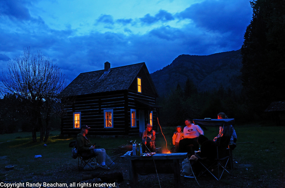 Sitting around the campfire at Bull River Guard Station, one of the original ranger stations on the Kootenai National Forest now used as a cabin rental. Bull River Valley, northwest Montana.