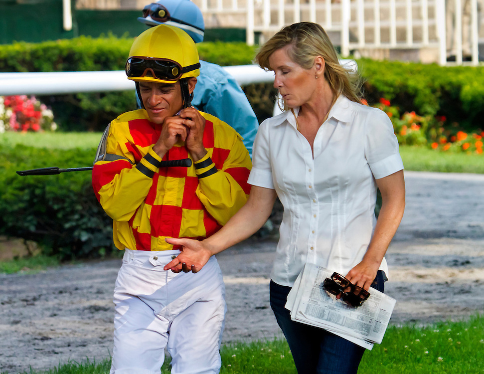 Veteran Jockey Cornelio Velasquez in the paddock talking to trainer Linda Rice, program in hand, before the ninth race. They won the race. It was Linda's 999th win.