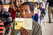09 JULY 2014 - ARANYAPRATHET, SA KAEO, THAILAND: A Cambodian migrant worker holds up his border crossing permit at the Thai Immigration One Stop Service Center in Aranyaprathet on the Thai-Cambodian border. More than 200,000 Cambodian migrant workers, most undocumented, fled Thailand in early June fearing a crackdown by Thai authorities after a coup unseated the elected government. Employers have been unable to fill the vacancies created by the Cambodian exodus and the Thai government has allowed them to return. The Cambodian workers have to have a job and their employers have to vouch for them. The Thai government is issuing temporary ID cards to allow them to travel openly to their jobs. About 800 Cambodian workers came back to Thailand through the Aranyaprathet border crossing Wednesday. The Thai government has opening similar service centers at three other crossing points on the Thai-Cambodian border.    PHOTO BY JACK KURTZ