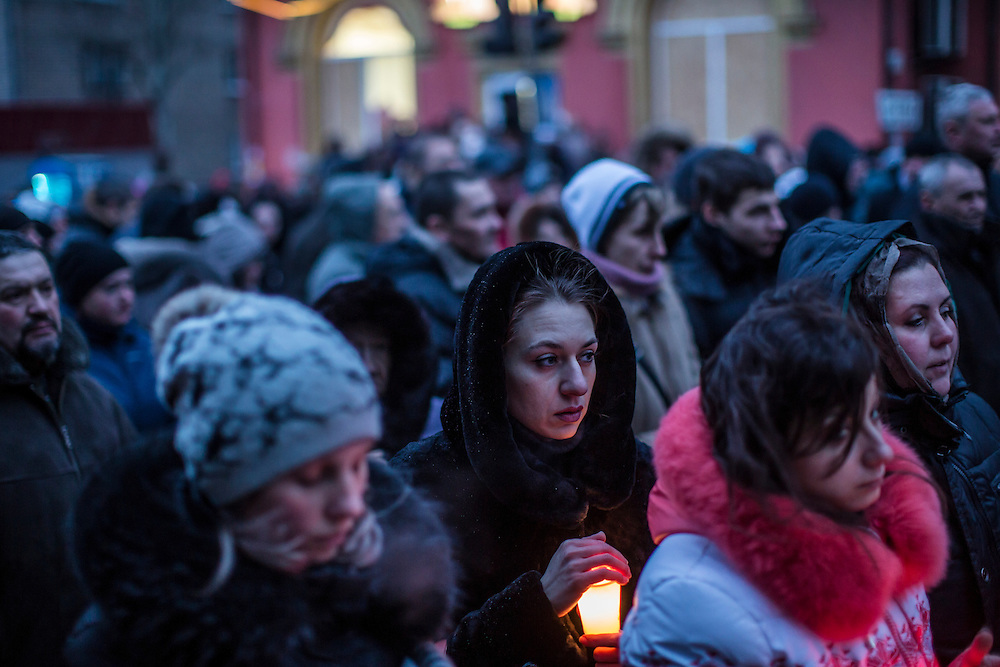 DONETSK, UKRAINE - JANUARY 24, 2015: A woman holds a candle at a memorial event for victims of a rocket strike that hit a trolleybus two days earlier in Donetsk, Ukraine. The attack killed at least eight civilians and injured many more. CREDIT: Brendan Hoffman for The New York Times