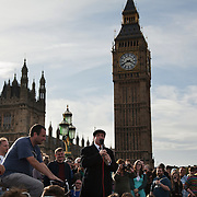 Mark Thomas, political stand-up comedia performing. The amp and speaker is powered by bicycle..The Health and Care Bill has been passed by Parliament and is due to go to the House of Lords. In protest against the bill which aim to deconstruct and privatise large parts of the NHS UK Uncut activists together with health workers and trade unionists blocked the Westminster Bridge from 1pm til 5.30pm.