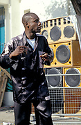 Black man dancing, wearing black and grey shirt with speakers in background, Notting Hill Carnival, UK, 2000's