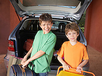 Portrait of two boys (6-11) carrying suitcases in front of car