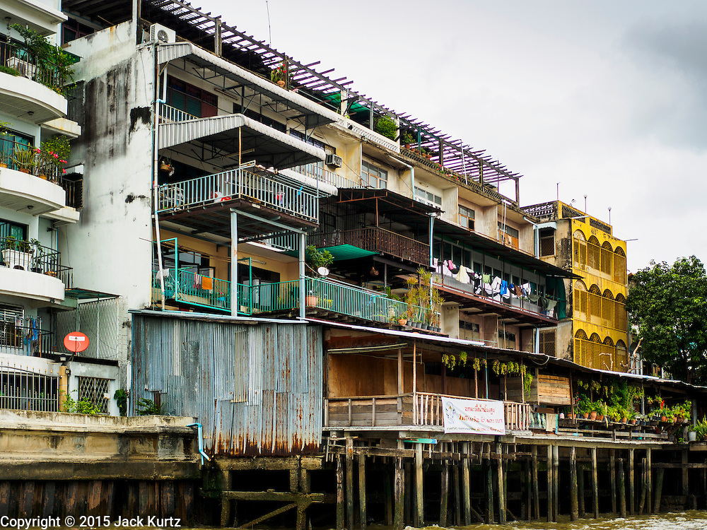 20 JULY 2015 - BANGKOK, THAILAND:   Housing on the Chao Phraya River south of Pin Klao Bridge and the planned redevelopment of the riverfront. The Chao Phraya promenade is development project of parks, walkways and recreational areas on the Chao Phraya River between Pin Klao and Phra Nang Klao Bridges. The 14 kilometer long promenade will cost approximately 14 billion Baht (407 million US Dollars). The project involves the forced eviction of more than 200 communities of people who live along the river, a dozen riverfront  temples, several schools, and privately-owned piers on both sides of the Chao Phraya River. Construction is scheduled on the project is scheduled to start in early 2016. There has been very little public input on the planned redevelopment.         PHOTO BY JACK KURTZ