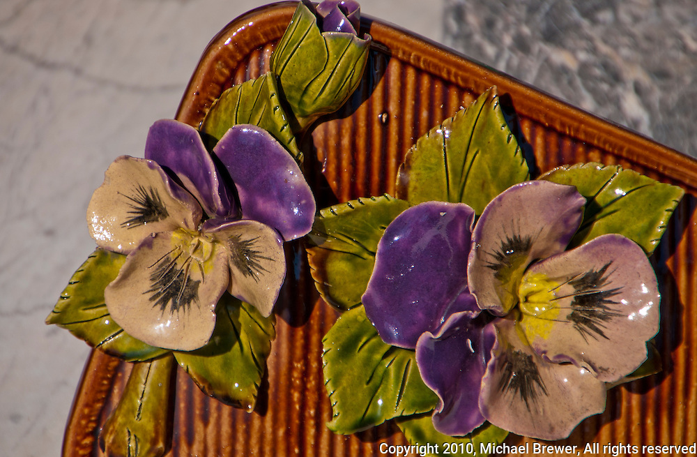 Detail of pretty majolica ceramic pansies grave decoration in Provence, France.