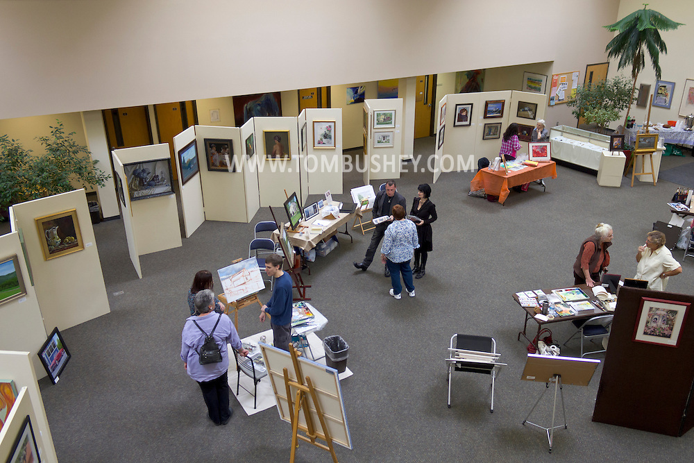 Middletown, New York - People watch artists work in the gallery at Orange Hall on the SUNY Orange campus during the Orange County Arts Council Open Studio Tour on Oct. 20, 2012.
