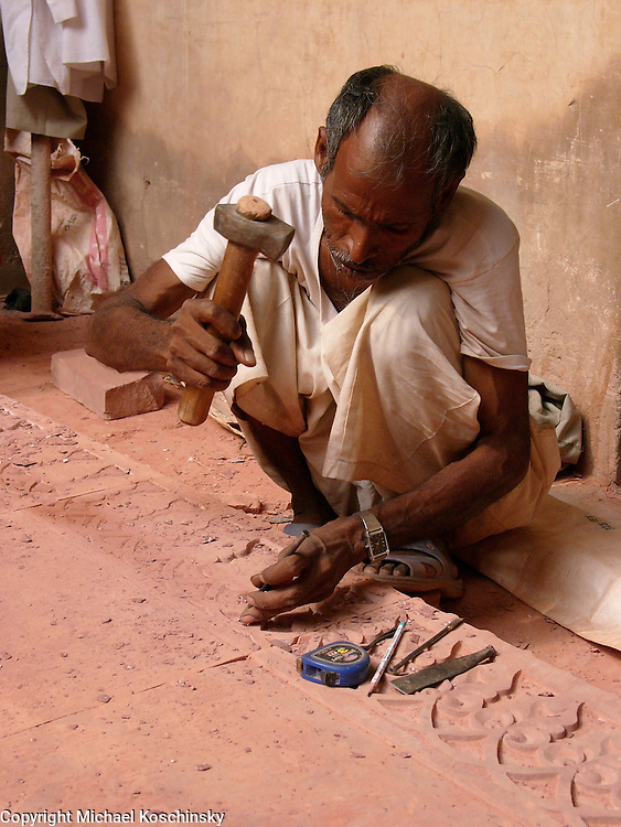 A stone mason restoring the sandstone carvings in the Fort of Agra