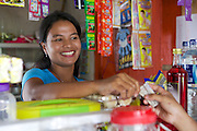 Jula Eha serving a customer in her shop outside the front of her house in a quiet residential area near the town of Bogor, Indonesia.<br /> <br /> Her shop had mixed success at first and she used to become demotivated, but after subscribing to Usaha Wanita she regained her motivation and started to think of more creative ways to make her business a success. <br /> <br /> As a result her profits have increased and she is now saving money in an education fund for her children. <br /> <br /> She has also been able to follow Usaha Wanita's advice on savings and investments and she has joined a savings scheme and purchases new fridges and display cabinets for her store.