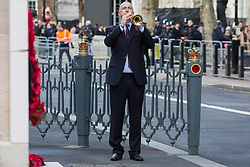London, UK. 10 November, 2019. A bugler plays 'The Last Post' in front of ex-services personnel from Veterans For Peace UK (VFP UK) taking part in the Remembrance Sunday ceremony at the Cenotaph. VFP UK was founded in 2011 and works to influence the foreign and defence policy of the UK for the larger purpose of world peace.