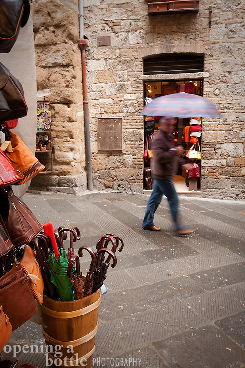 A pedestrian walks with an umbrella in the rain, San Gimignano, Tuscany, Italy.