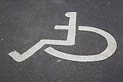 Wheelchair logo sign on tarmac for disabled parking area, UK