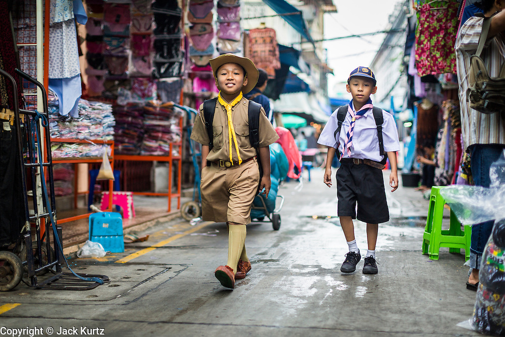06 JUNE 2013 - BANGKOK, THAILAND: A Boy Scout and a Cub Scout walk from their home to their school through Bobae Market in Bangkok. Bobae Market is a 30 year old famous for fashion wholesale and is now very popular with exporters from around the world. Bobae Tower is next to the market and  advertises itself as having 1,300 stalls under one roof and claims to be the largest garment wholesale center in Thailand.       PHOTO BY JACK KURTZ