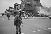 Soldier standing guard in a Washington, D.C., street with the ruins of buildings that were destroyed during the riots that followed the assassination of Martin Luther King Jr., 8 April 1968. Photographer:  Warren K  Leffler.