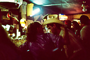 A woman with her arm around a man wearing a cowboy hat at the bar in the Rod and Gun Club in Beardstown, Illinois