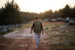 A rebel soldier who left the Syrian army and joined the Free Syrian Army (FSA) walks to a base camp in a secret location where around 30 soldiers and some civilians are gathering in the countryside of Aleppo, northwestern Syria, on April 28, 2012. Photo by Daniel Leal-Olivas / i-Images...