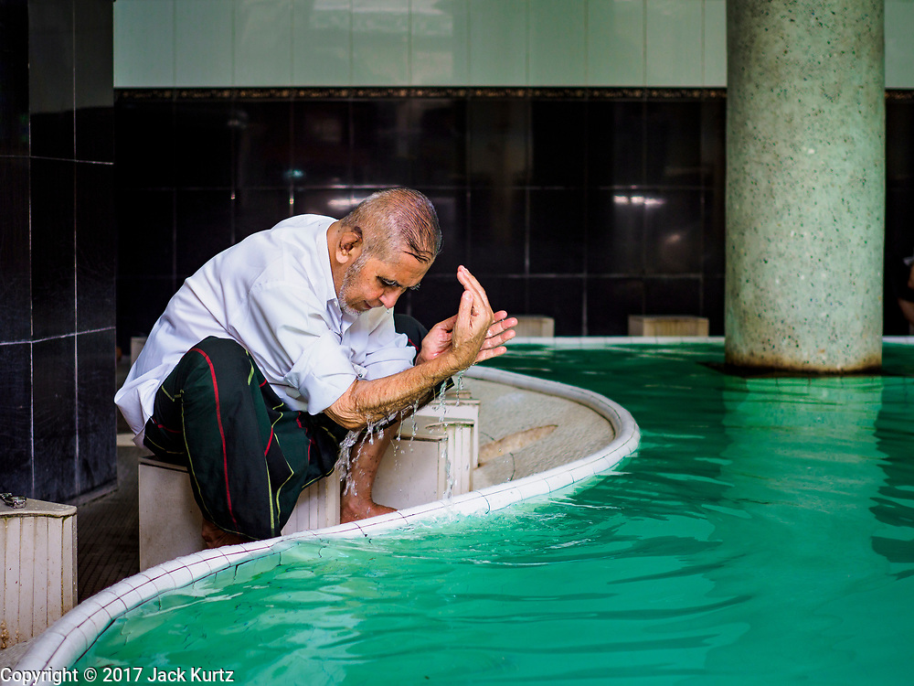 "24 NOVEMBER 2017 - YANGON, MYANMAR: A Muslim man performs ablutions before Friday prayers in Surtee Sunni Jumma Mosque in Yangon. Many Muslims in overwhelmingly Buddhist Myanmar feel their religion is threatened by a series of laws that target non-Buddhists. Under the so called ""Race and Religion Protection Laws,"" people aren't allowed to convert from Buddhism to another religion without permission from authorities, Buddhist women aren't allowed to marry non-Buddhist men without permission from the community and polygamy is outlawed. Pope Francis is to arrive in Myanmar next week and is expected to address the persecution of the Rohingya, a Muslim ethnic minority in western Myanmar. Some Muslims and Christians are concerned that if the Pope's comments take too strong of pro-Rohingya stance, he could exacerbate religious tensions in the country.  PHOTO BY JACK KURTZ"
