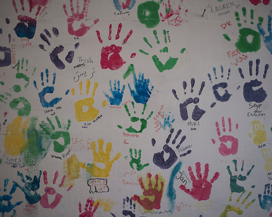 Children's handprints decorate a wall in the former refugee camp at the port of Lakki.<br />