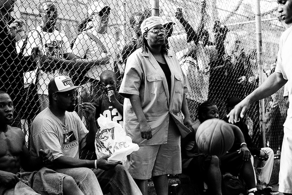 "April 20th 2005. New York, New York. United States..Located in the heart of Greenwich Village, the West 4th Street basketball Court, known as ""The Cage"", offers no seating but attracts the best players and a lot of spectators as soon as spring is around the corner..Half the size of a regular basketball court, it creates a fast, high level of play. The more people watch, the more intense the games get. « The Cage » is a free show. Amazing actions, insults and fights sometimes, create tensions among and inside the teams. The strongest impose their rules. Charisma is present..""The Cage"" is a microcosm. It's a meeting point for the African American street culture of New York. Often originally from Jamaica or other islands of the Caribbean, they hang out, talk, joke, laugh, comment the game, smoke… Whether they play or not, they're here, inside ""The Cage"". Everybody knows everybody, they all greet each other, they shake hands and hug: ""Yo, whasup man?"""