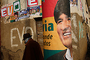 An indigenous man walks past a wall full of political propaganda from president Evo Morales in the highlander village of Warisata, , Saturday, Aug. 2, 2008.  Morales is on a political campaign throughout the country to guarantee that he will obtain majority on a nation-wide recall vote scheduled for next August, 10. (AP Photo/Dado Galdieri)